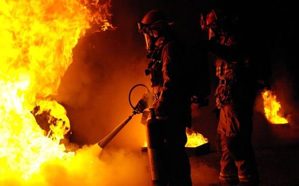 Bombeiros apagando fogo com extintor