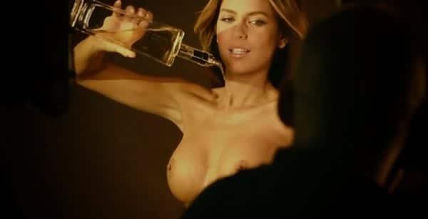 Loira jogando garrafa de whisky nos peitos