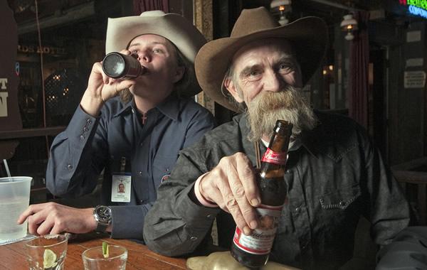 Velho rindo e segurando garrafa de cerveja