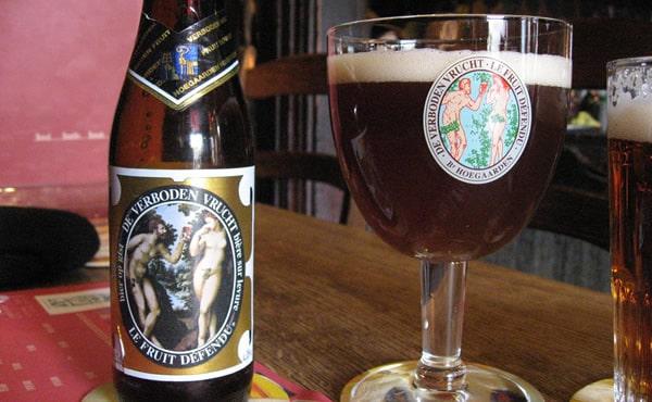 Garrafa e copo da cerveja Hoegaarden Forbidden Fruit
