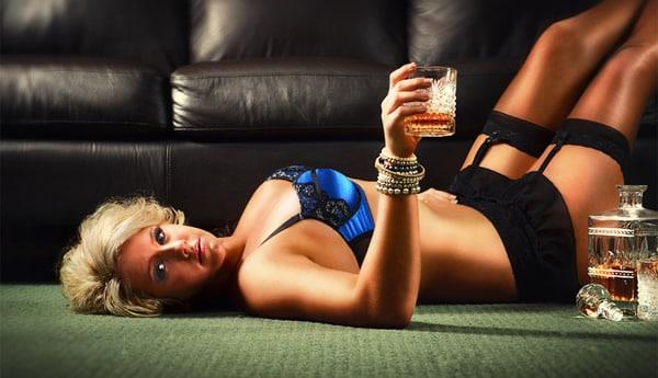 Loira gostosa deitada e com um copo de whisky