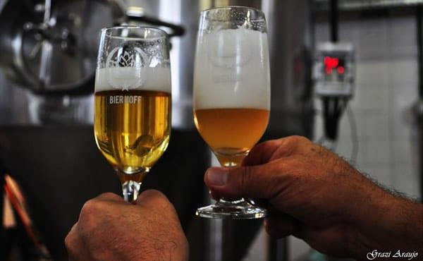 Taças de cerveja na mão