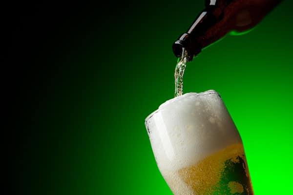 Garrafa botando cerveja numa tulipa