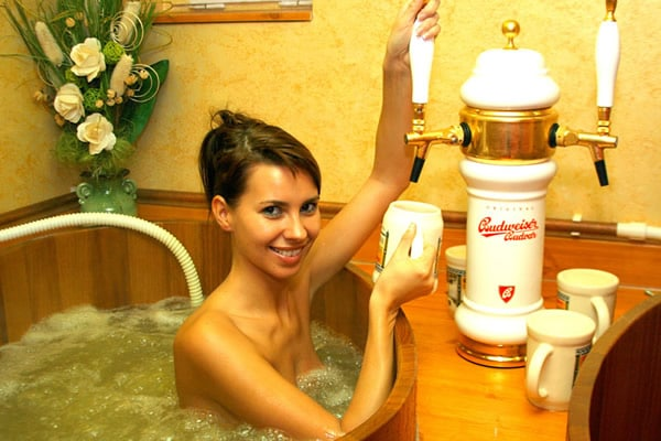 Mulher tirando chopp e tomando banho num barril cheio de cerveja