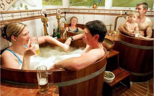 Galera dentro de um barril tomando banho de cerveja