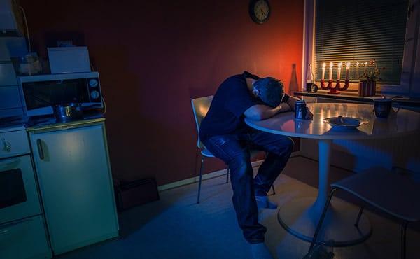 Homem sentado numa mesa chorando e bebendo cerveja