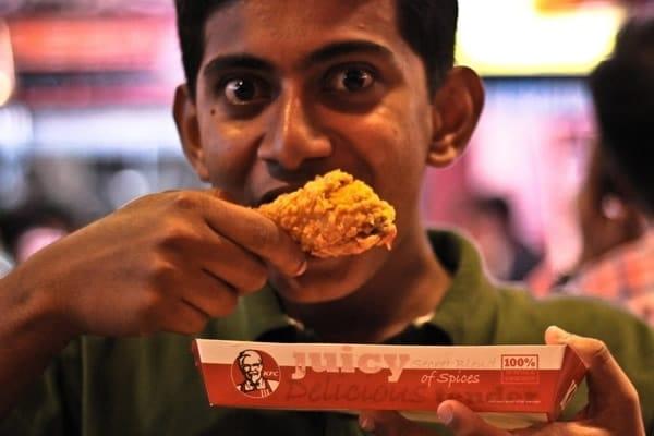 Garoto comendo frango kfc