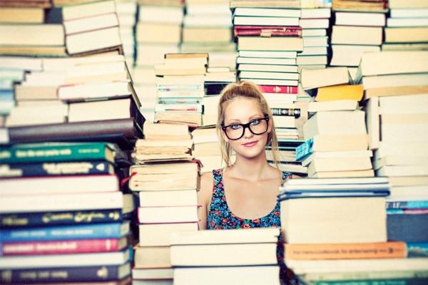 Menina cercada de livros por todos os lados