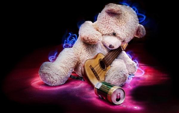 Urso tocando violão e bebendo cerveja, simbolizando a bebida e música