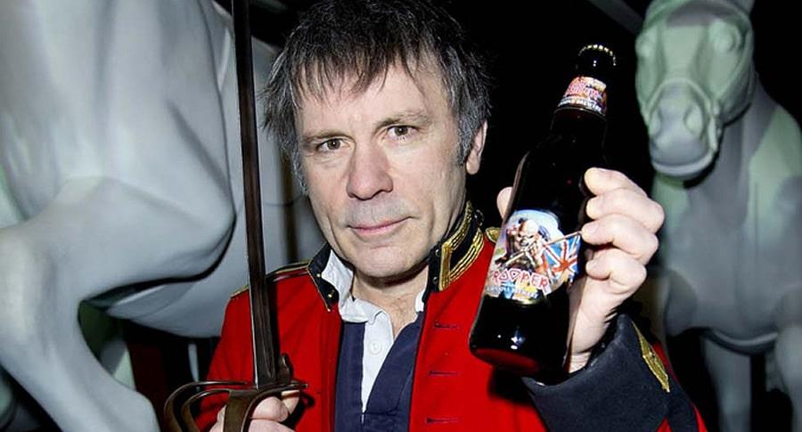 Bruce Dickinson segurando a garrafa da cerveja do Iron Maiden