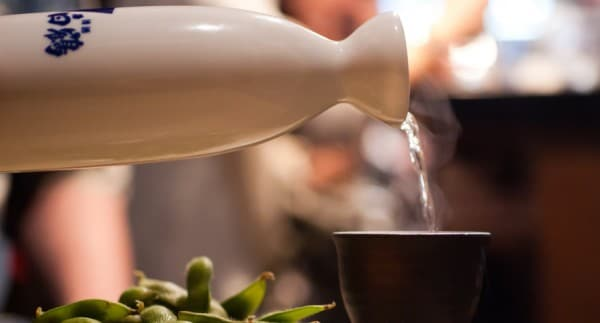 Garrafa colocando Sake num copo