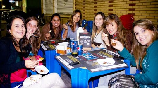 Mulheres que bebem cerveja e comendo num boteco