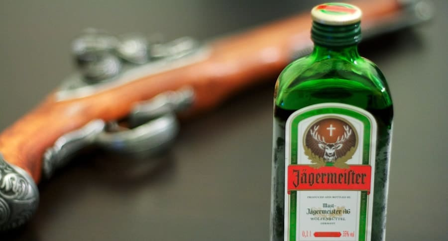 Arma e uma garrafa de Jagermeister