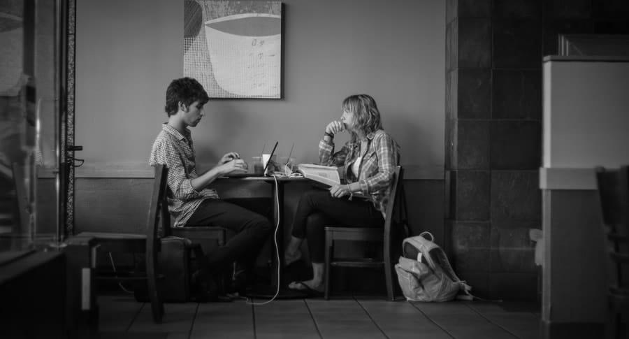 Casal sentado no bar com computador e conversando