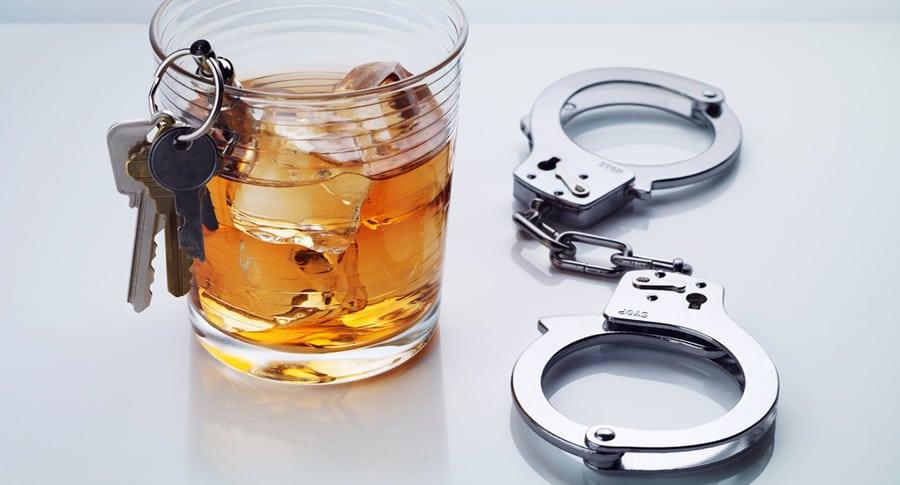 Copo de whisky, chave de carro e algema simulando bebida e direção