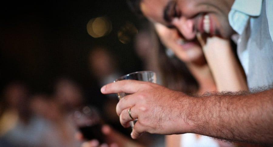 Homem sorrindo segurando um copo de cerveja