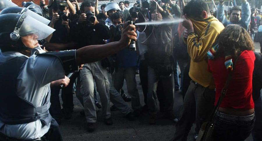 Policial jogando gás de pimenta