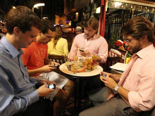 Homens no boteco conversando no celular