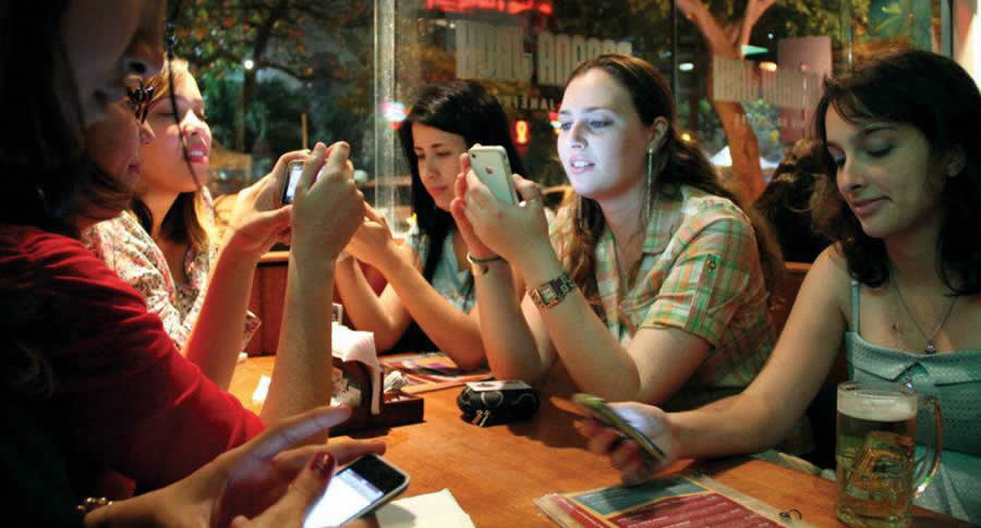 Mulheres sentadas numa mesa de bar mexendo no celular