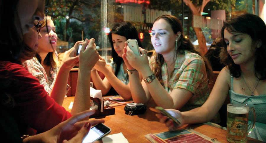 Mulheres sentadas numa mesa de bar mexendo no celular