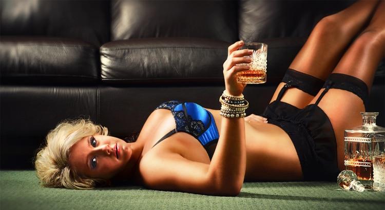 Mulher deitada com uma copo de whisky mostrando amor e sexo