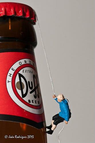 Boneco escalando garrafa de cerveja