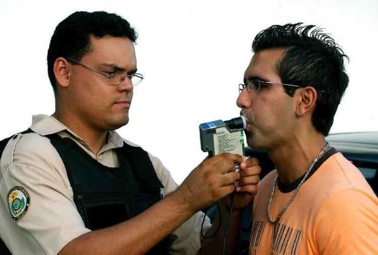 Homem tentando driblar o bafômetro