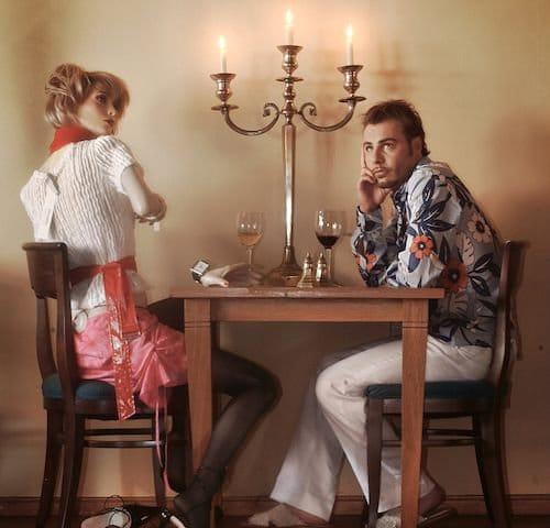 Homem sentado na mesa com uma boneca