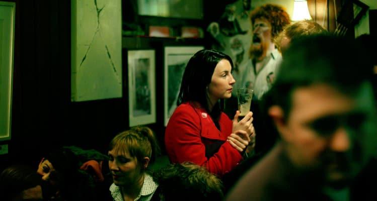 Mulher bebendo sozinha num bar
