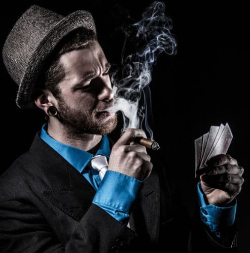 Homem fumando charuto e jogando poker