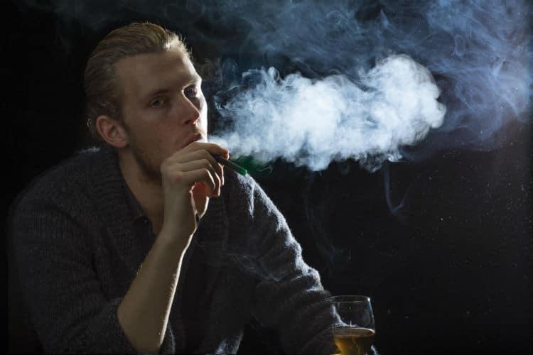 homem fumando e bebendo vinho