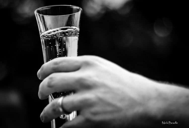 mão segurando taça de champagne