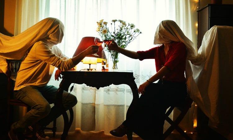 Casal se encontrando com lençol no rosto