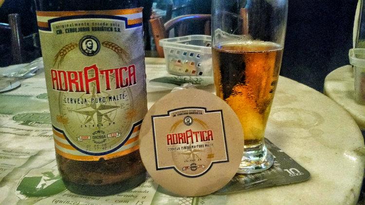 Garrafa, bolacha e copo da Adriática, uma cerveja para desbravadores