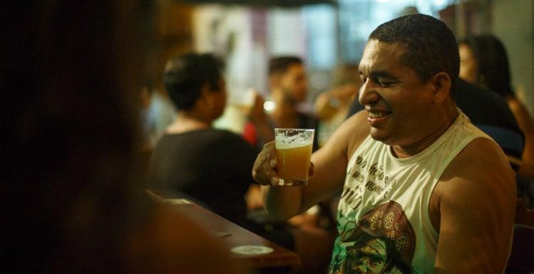 Morador bebendo cerveja no Bistrô Estacao R&R no Complexo do Alemão