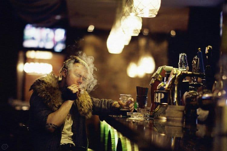 homem fumando dentro de um bar
