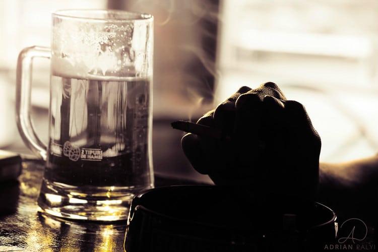 mão segurando cigarro e caneca de cerveja