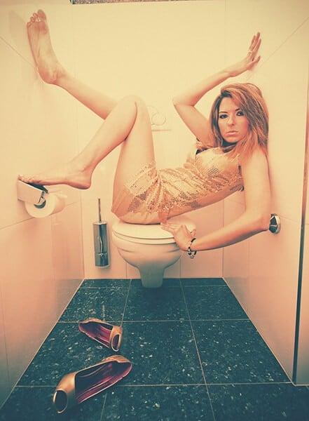 mulher fazendo malabarismo no banheiro feminino