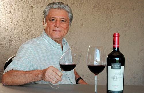 Euclides Penedo Borges segurando taças de vinho
