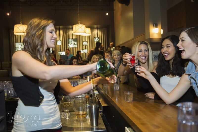 mulheres bebendo em pé e bartender mulher