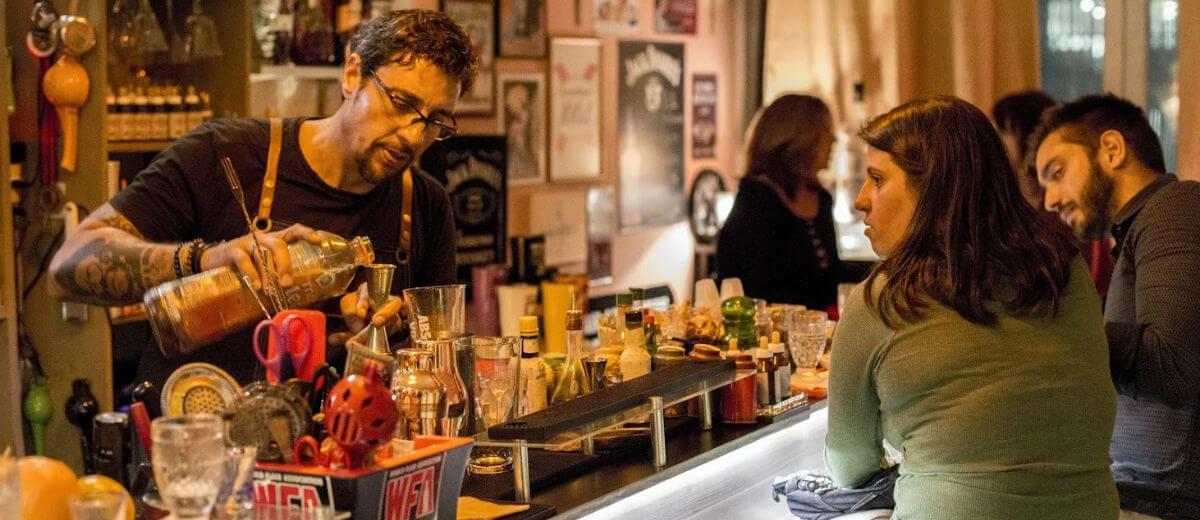 walter garin preparando drink no balcão com casal olhando