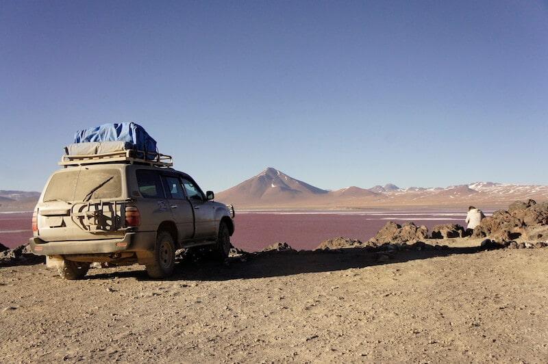 carro 4x4 com montanha ao fundo e lagoa vermelha no mochilão