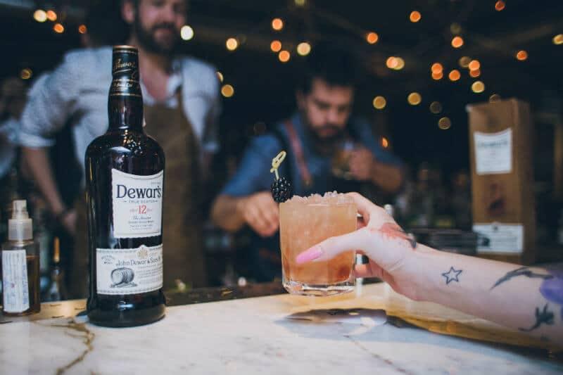 garrafa dewar's e braço segurando drink