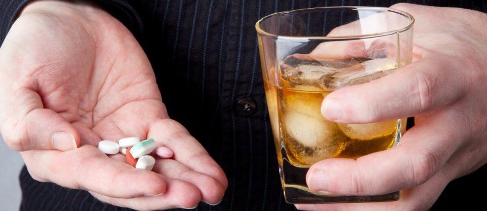 mão segurando alcool e antidepressivos