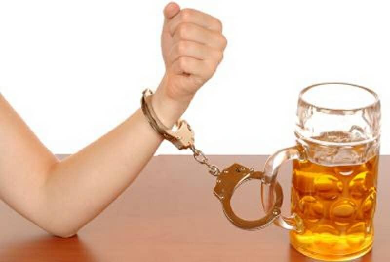 braço preso por algemas numa caneca de cerveja