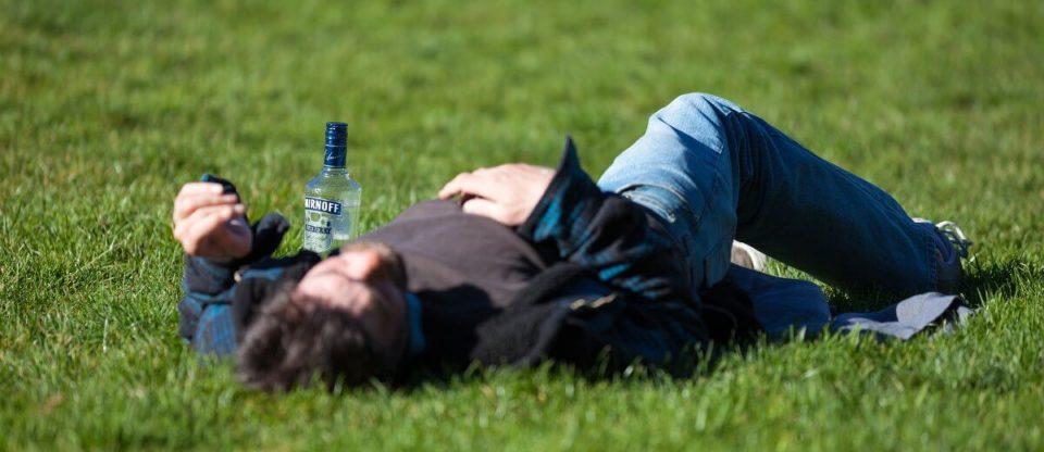 homem de ressaca deitado no mato