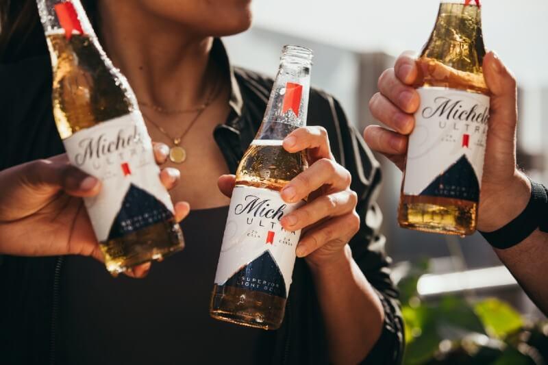 Pessoas brindando com a cerveja Michelob Ultra