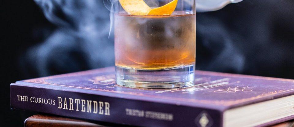 livro com um whisky em cima